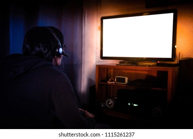 Young male gamer with glasses and headset playing video game at home in the dark room using game console controller watching at LED TV. Gaming and entertainment concepts