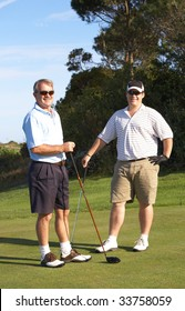 Young male golfer with his senior father ready to tee off on a beautiful summer day