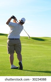 Young male golfer hitting the ball from the fairway on a beautiful summer day