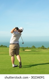 Young male golfer hitting the ball from the green on a beautiful summer day