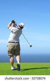 Young male golfer hitting the ball from the tee box next to the ocean on a beautiful summer day