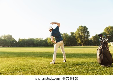 Young male golfer stretching muscles before starting the game at the green field
