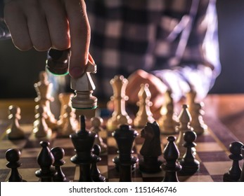 young male grandmaster hand making next move playing chess in dark place on a tournament