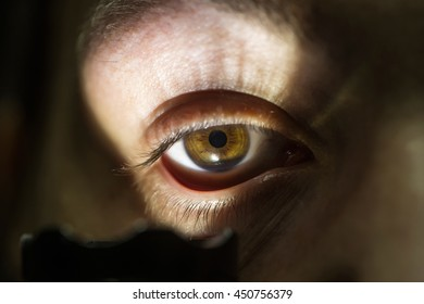 young male with hairy eyebrow on serious face lighting on eye with flashlight in studio, closeup