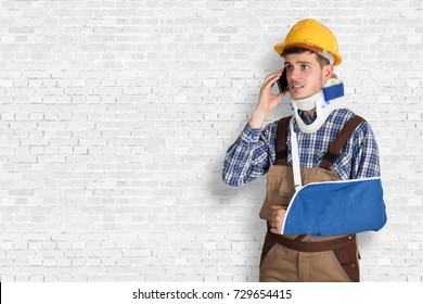 Young Male Handyman With Fractured Hand Calling On Mobile Phone