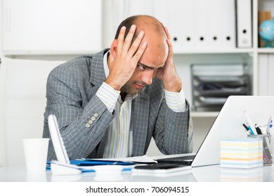 Young male having lot of work and problems in the office