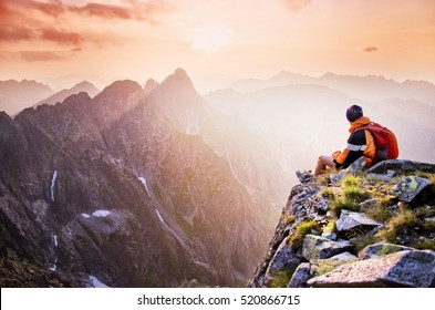 Young male hiker with backpack relaxing on top of a mountain during calm summer sunset - scenery from vacation - photo with space for your montage.