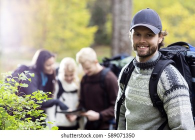 Young Male Hiker With Friends Discussing In Background