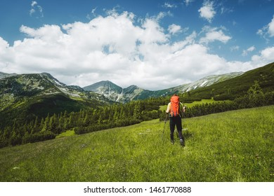 Young male hiker hiking with backpack and trekking sticks in summer in the Retezat Mountains in Romania