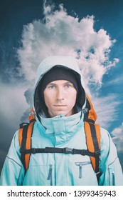 Young male hiker on cloudy landscape background looking at camera. Front view. Active lifestyle and tourism. Vertical.