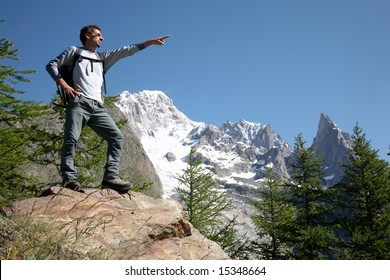 Young male hiker pointing to somewhere; mountain scenic, Mont Blanc, Italy.