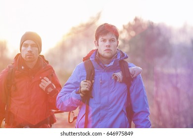 Young male hikers looking away in field