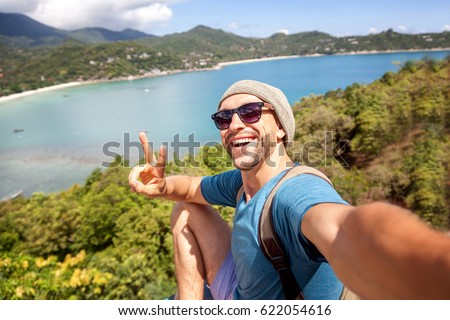 Young male hipster traveler doing selfie overlooking the tropical sea. Adventure, vacation, wonderlust, internet, technology concept.