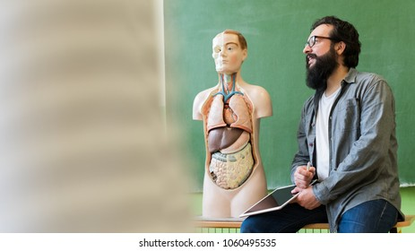 Young male hispanic teacher in biology class, holding digital tablet and teaching human body anatomy, using artificial body model to explain internal organs.