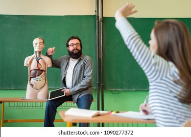 Young male hispanic teacher in biology class, holding digital tablet and teaching human body anatomy, using artificial body model to explain internal organs. Female student raising her hand.