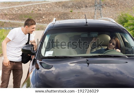 Young male hitchhiker looking for a lift talking to a female driver through the passenger window of her car as he tries to persuade her to give him a ride