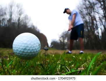A young male hits a golfball down the fairway.