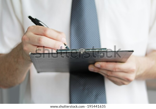 Young male holding a tablet and a pen close up