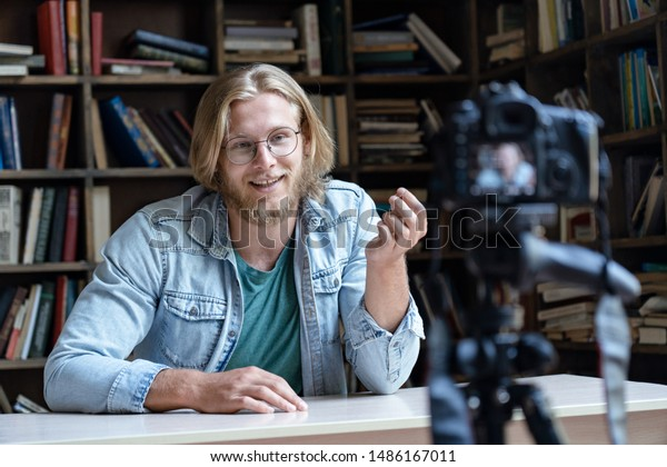 Young male influencer tutor teacher blogger talking looking at professional dslr camera shooting vlog, recording educational training, filming video course tutorial for channel sit at desk in library