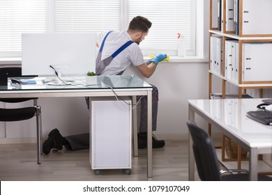 Young Male Janitor Cleaning The Window Sill With Sponge In Office