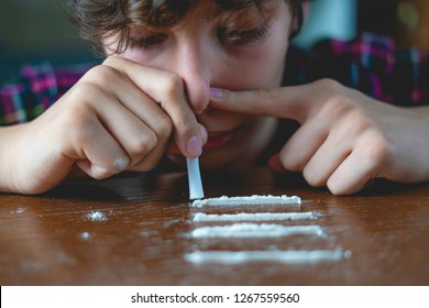 young male junkie sniff and snort the cocain on the wooden table