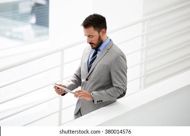 Young male lawyer searching information on touch pad during work break after business meeting with client, successful man employer checking e-mail via digital tablet while standing in office interior
