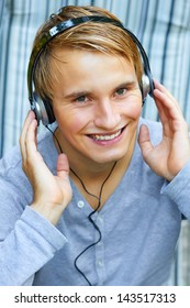 Young male listening to music via headphones