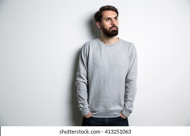 Young male in long sleeved sweatshirt on light grey background. Mock up