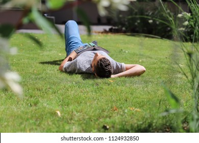 Young male lying in the grass and relaxing after reading with an open book on a sunny summer day, concept of relaxation, student lifestyle, self education, break between studies, power nap