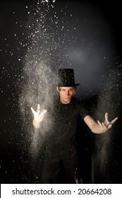 Young male magician throwing magic powder