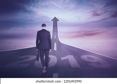 Young male manager holding a suitcase while walking above numbers 2019 toward end road shaped upward arrow