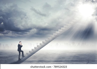 Young male manager talking on the mobile phone while walking on the staircase toward sunlight in the sky