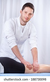 Young male masseur massaging female patient's thigh