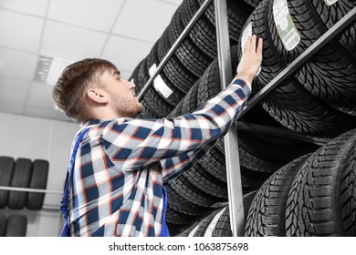 Young male mechanic with car tires in automobile service center