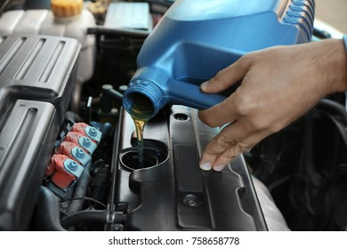 Young male mechanic pouring engine oil from canister, closeup