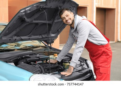 Young male mechanic repairing car at service station
