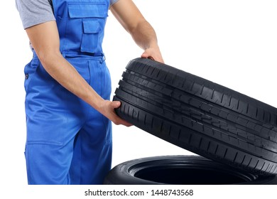 Young male mechanic in uniform with car tires on white background