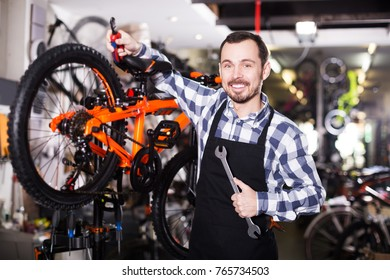 Young male mechanic working for assembly of bicycles in shop workroom
