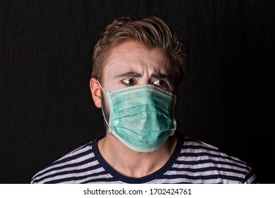 Young male mime artist upper thorso and head, making tired, disgust or displeased expression only with eyes, wearing medical face mask during coronavirus pandemy, on dark background.