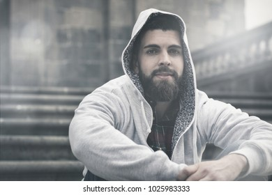 Young male model with full beard covers head with grey hoodie sitting on stairs in old town. Hip hop, rapper style concept. Sun flare effect