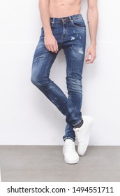 Young male model in jeans with white sneakers on gray background
