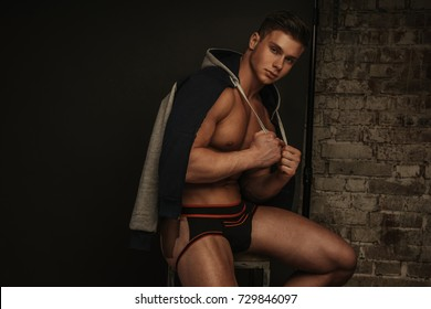 Young male model in jocks underwear and sport jacket sitting in the studio