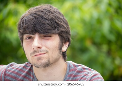 A young male model is looking attractively into the camera winking with one eye