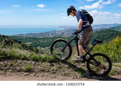 Young male mountain biker on an electric bicycle balancing on the border of a mountain road, Barcelona Spain in the background