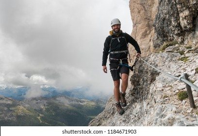 young male mountain climber on a steep and exposed Via Ferrata in Alta Badia in the South Tyrol in the Italian Dolomites