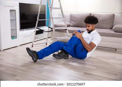 Young Male Mover Falling From Ladder In The Living Room Having Pain In The Knee