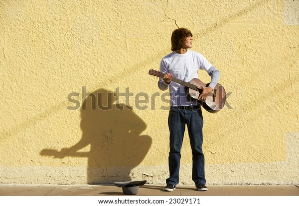 Young male musician alone on the sidewalk with guitar