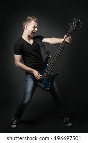 young male musician playing a six-string bass guitar isolated on dark background