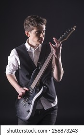 Young male musician is playing a six-string bass guitar isolated on dark background.
