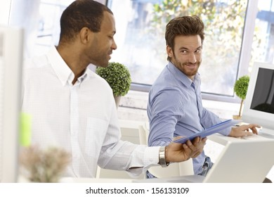 Young male office workers sitting at desk, one passing folder to the other in bright office.